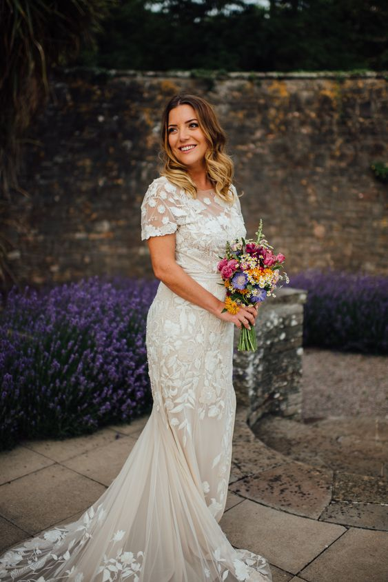 a lace applique mermaid wedding dress with short sleeves, a high neckline and a long train