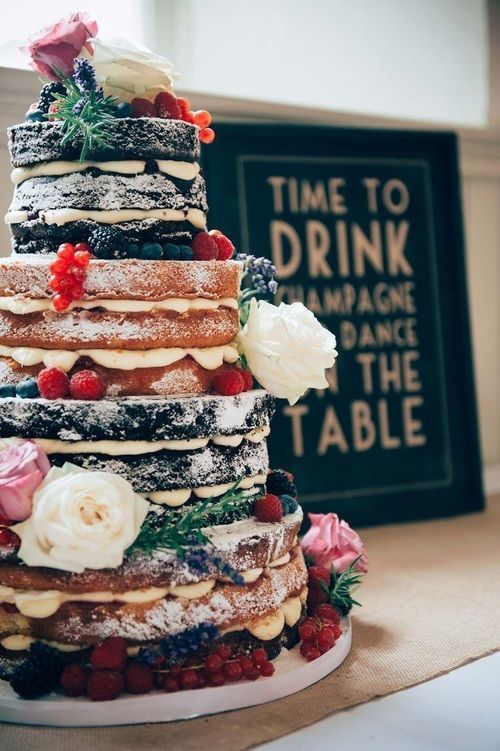 a large naked wedding cake with fresh berries and blooms and sugar powder on top looks super yummy
