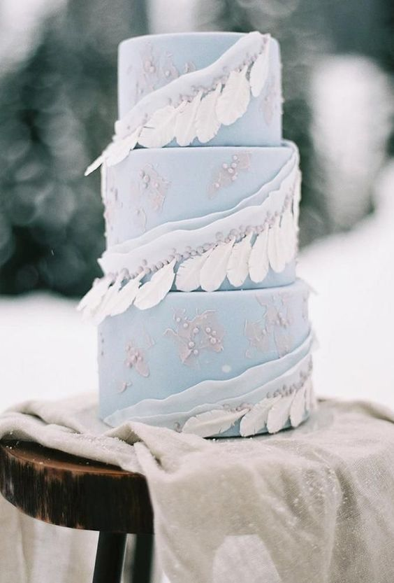 a light blue wedding cake with sugar beads, ribbons with beads and white feathers is a gorgeous idea for a winter boho wedding
