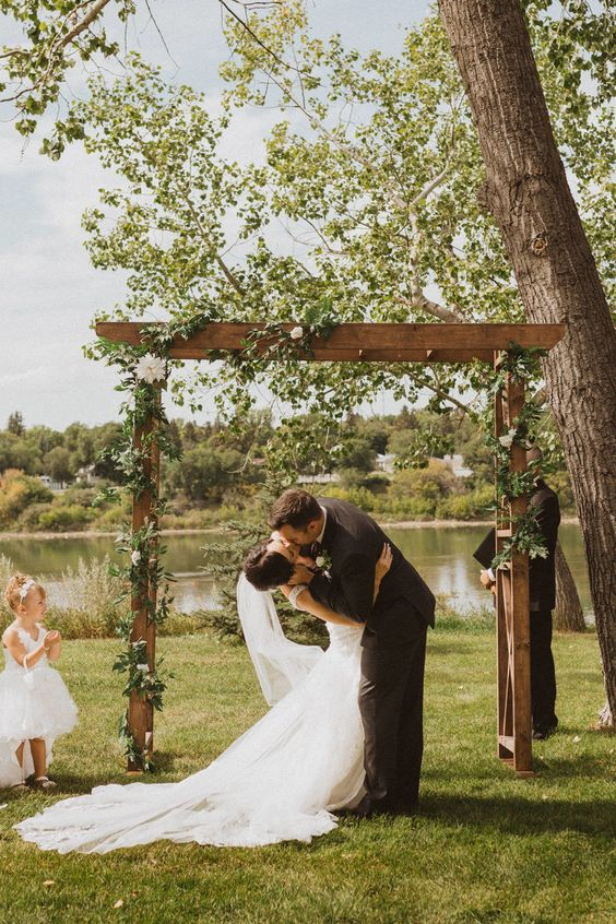 a lovely backyard wedding arch decorated with greenery and white blooms and with a pretty view of the lake