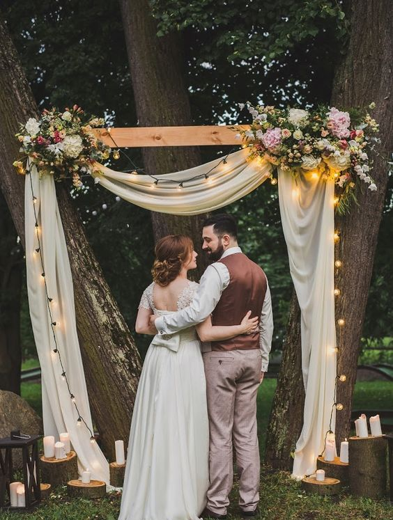 a lovely backyard wedding arch done with white fabric, lights, pastel and white blooms and candles on the ground