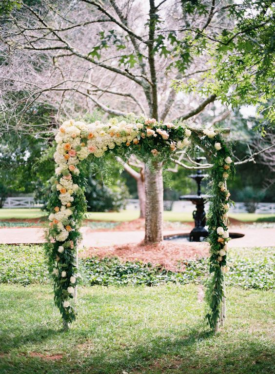 a lovely greenery, neutral and pastel bloom wedding arch can be installaed in any backyard for a chic wedding