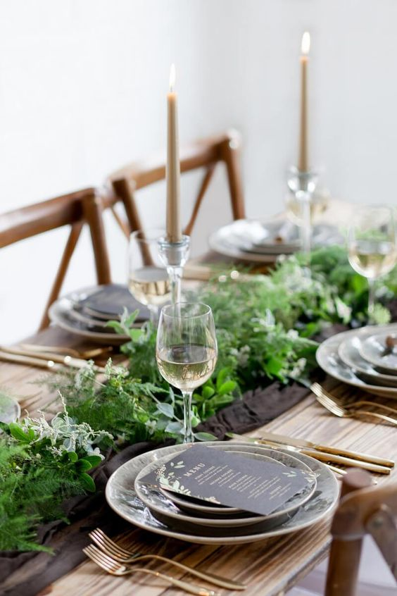 a lush and wild greenery table runner combined with a brown fabric one on an uncovered table