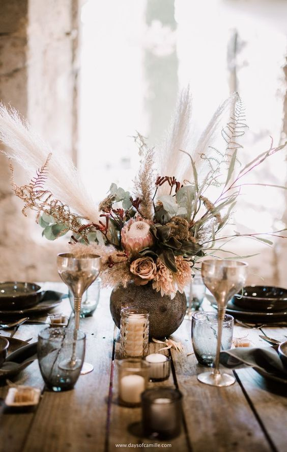 a lush boho wedding centerpiece with pink and mauve blooms, greenery, herbs and pampas grass