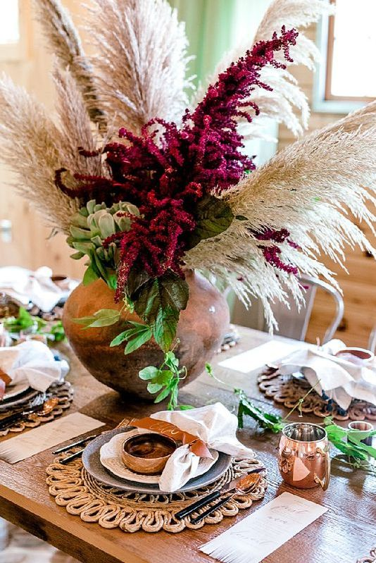 a lush boho wedding centerpiece with purple blooms, greenery and pampas grass for a bright touch