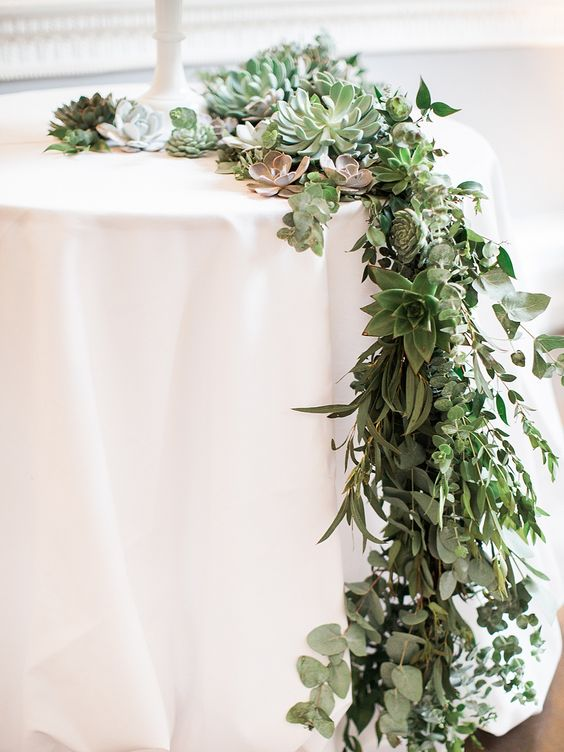 a lush eucalyptus and succulent table runner features much texture and various shades of succulents, too