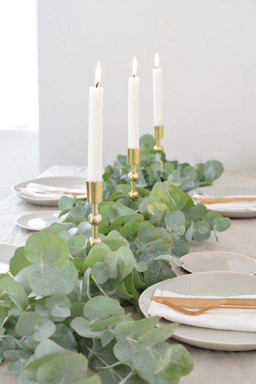 a lush eucalyptus table runner combined with gold candle holders and tall candles is timeless classics