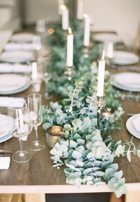 a lush eucalyptus table runner with mercury glass candle holders and metallic holders looks chic