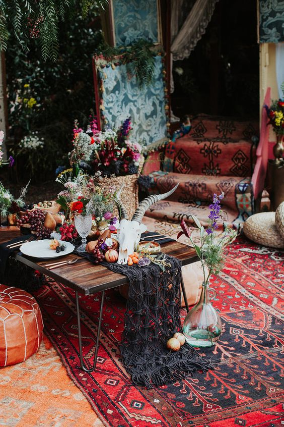 a lush picnic tablescape with a black macrame runner, an animal skull, fruits and veggies on top plus greenery