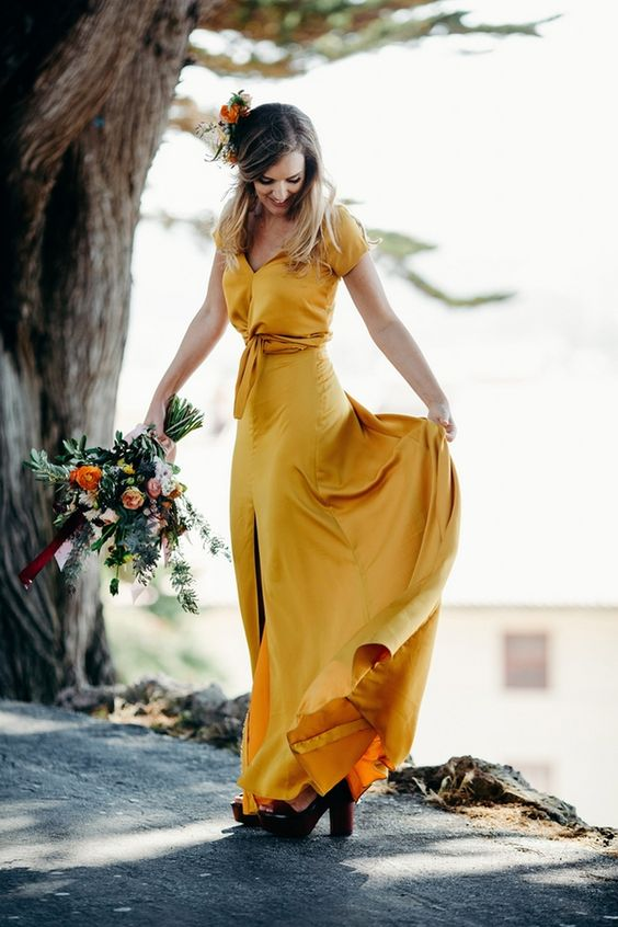 a marigold A-line wedding dress with a tied up bodice, a front slit and a short train for a non-traditional bride