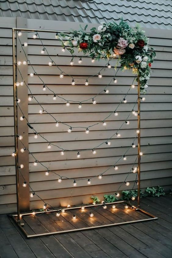 a metallic wedding arch with lush blooms and greenery and lights all over the arch is amazingly chic and beautiful