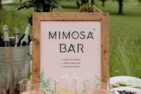 a mimosa bar with a chic sign and lots of juices in jars – make your own mimosa yourself