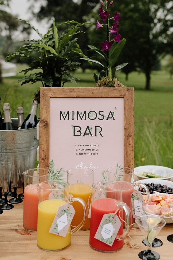a mimosa bar with a chic sign and lots of juices in jars - make your own mimosa yourself