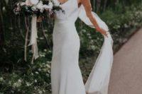 a minimalist high waist plain wedding dress with spaghetti straps, a train and a veil for a minimal bride