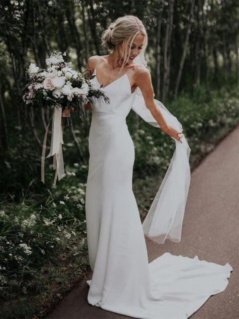 a minimalist high waist plain wedding dress with spaghetti straps, a train and a veil for a minimal bride