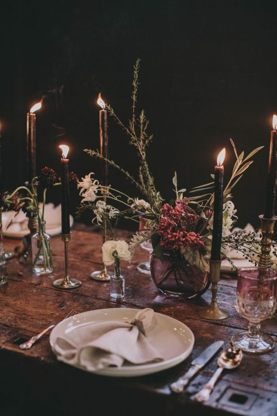 a moody boho wedding centerpiece with white and bright blooms and herbs plus black candles