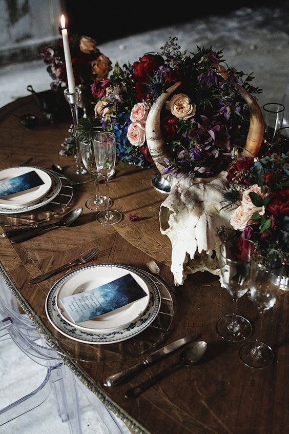 a moody boho wedding tablescape with patterned plates, an animal skull, lush florals, candles and greenery