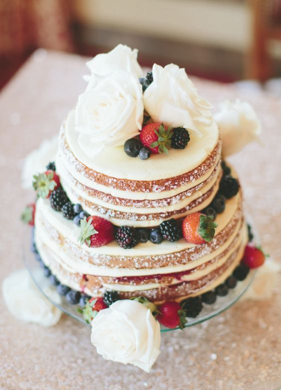 a mouth-watering naked wedding cake with white blooms and fresh berries is a lovely dessert for a rustic wedding