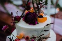 a naked wedding cake with bright blooms, berries, and a teepee on top with moss and bold dramatic flowers