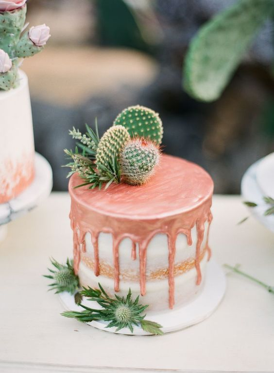 a naked wedding cake with copper dripping, succulents, cacti and thistles on top for a desert boho wedding
