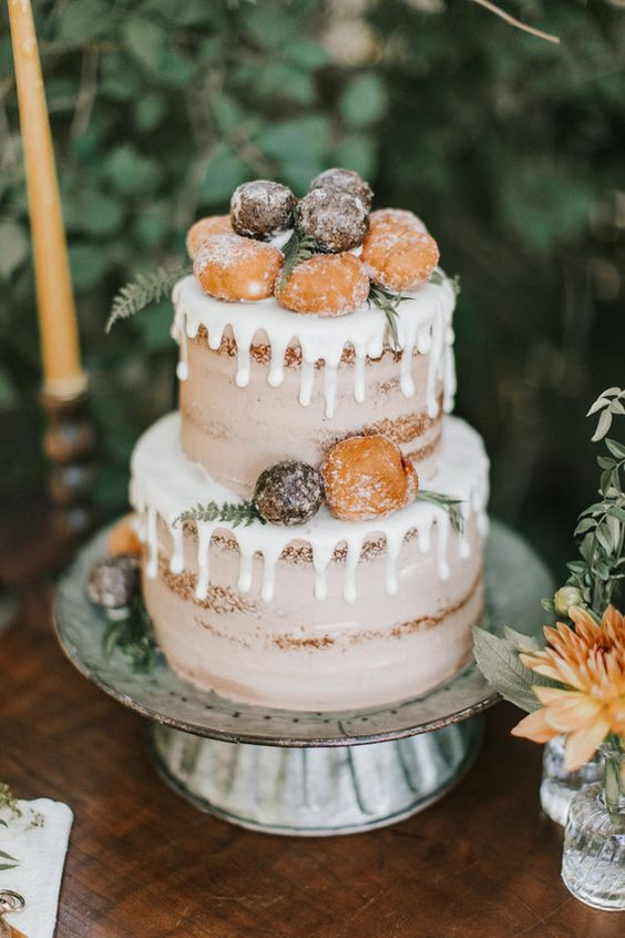 a naked wedding cake with creamy drip, donuts, greenery and fern is a cool wedding dessert for a rustic wedding