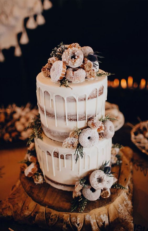 a naked wedding cake with creamy drip, with wildflowers, thistles and glazed donuts for a winter rustic wedding