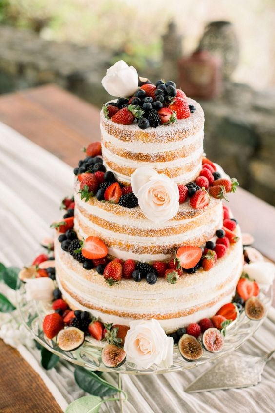 a naked wedding cake with fresh berries and blush blooms is a nice option for a summer rustic wedding