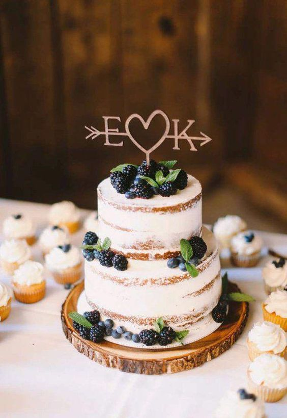 a naked wedding cake with fresh berries and mint and a cute topper is perfect for a rustic wedding