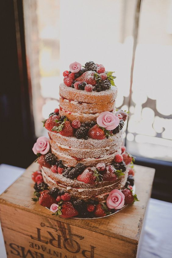 a naked wedding cake with fresh berries and pink sugar blooms is a delicious dessert for a summer rustic wedding