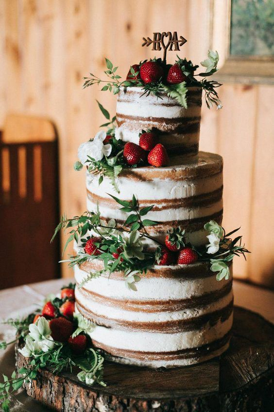 a naked wedding cake with fresh strawberries, greenery and white blooms plus a topper for a summer rustic wedding