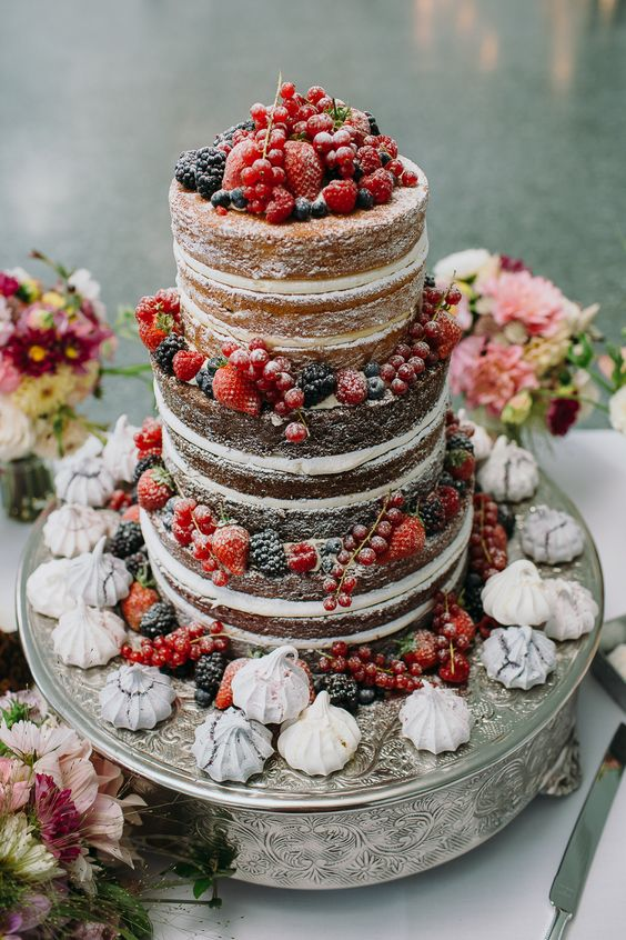 a naked wedding cake with lots of berries and meringues is a lovely idea for a rustic wedding