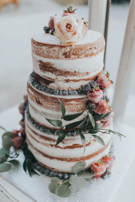 a naked wedding cake with sugared berries and greenery for a summer rustic wedding