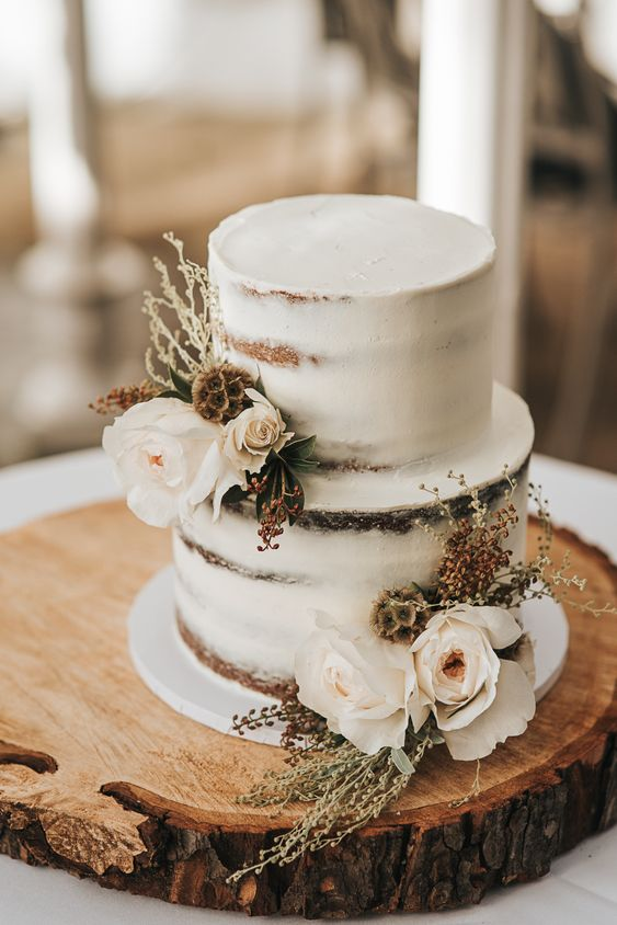 a naked wedding cake with white blooms and dired ones for a chic fall rustic wedding