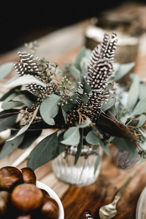 a natural boho wedding centerpiece of eucalyptus and feathers is a beautiful idea