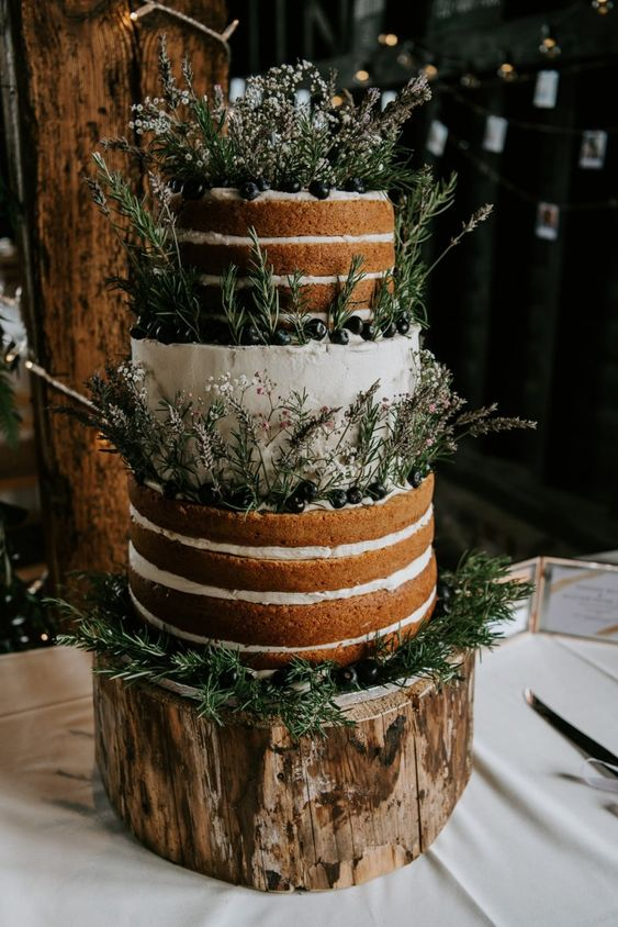 a partly naked wedding cake with lots of greenery, wildflowers and fresh berries for a rustic wedding