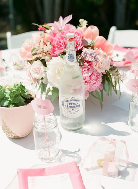 a pink and blush bridal shower table with pink linens, pink pots with greenery and lush pink blooms