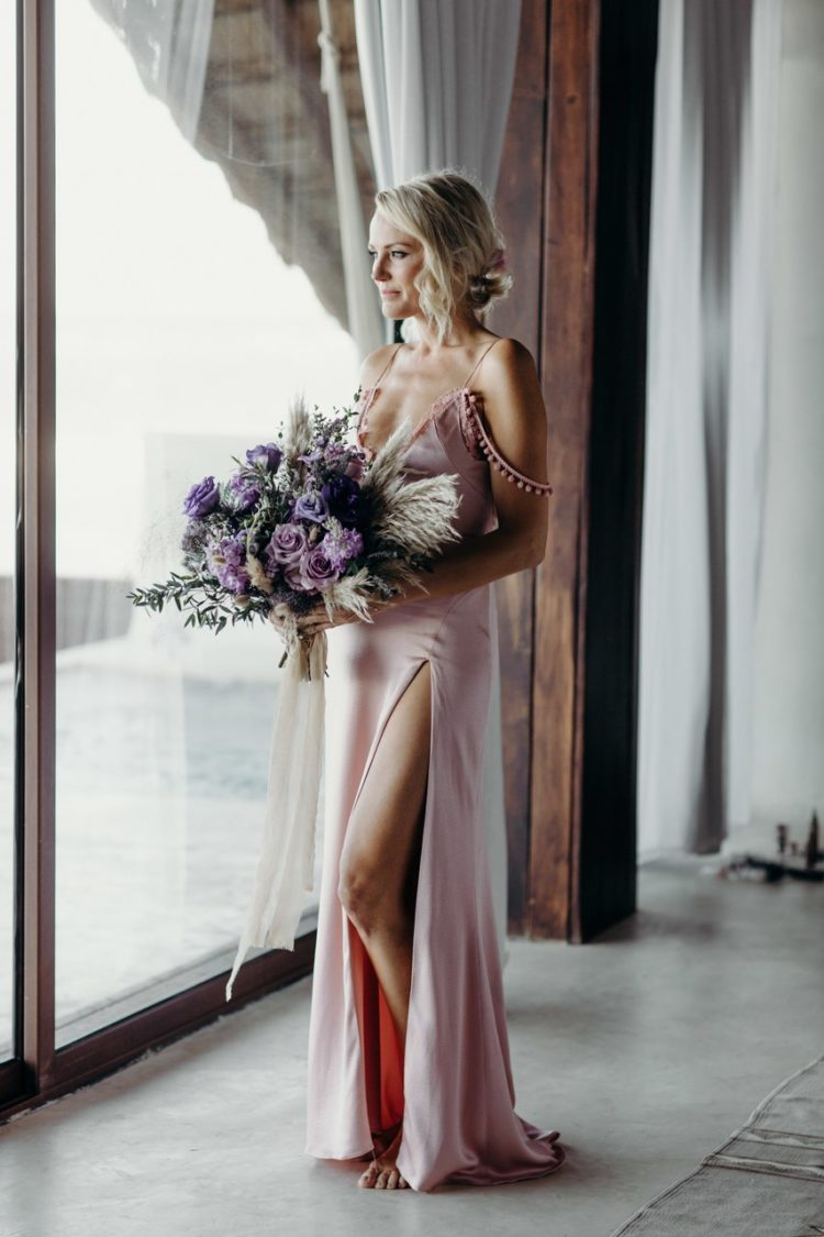 a pink silk slip wedding dress with pompoms, a thigh high slit and a deep neckline worn by Malin Akerman