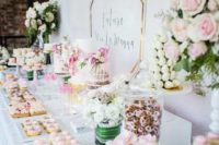 a pink sweets bar with various kinds of pink and blush sweets, cakes with pink blooms and greenery