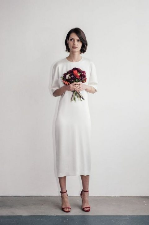 a plain white silk wedding dress with short sleeves and a high neckline plus red heels for an accent