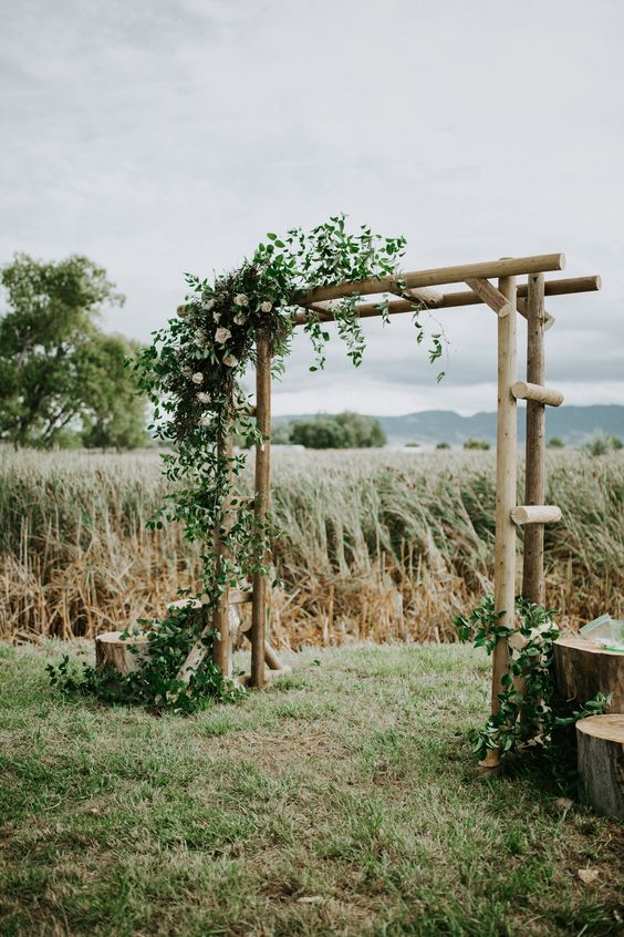 a pretty and simple rustic wedding arch composed of logs, with greenery and white blooms is ideal for a backyard wedding