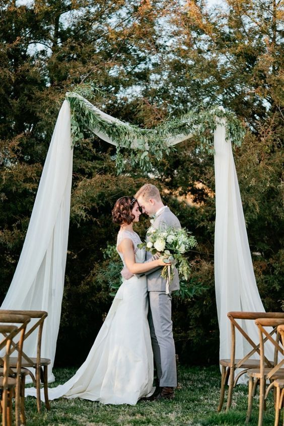 a pretty backyard wedding ceremony space with white fabric and greenery on top and wooden chairs is romantic and lovely