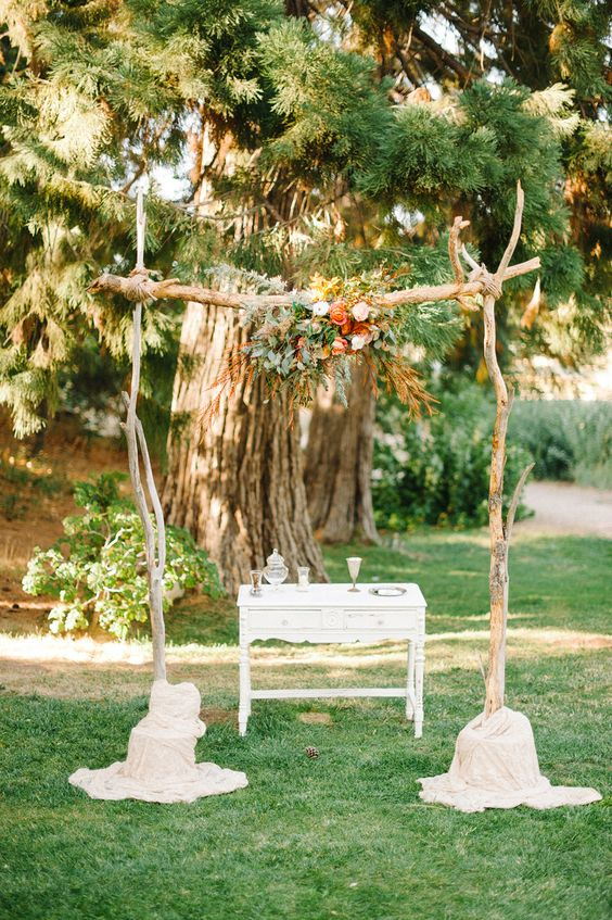 a pretty rustic wedding arch of branches, greenery, pastel blooms and foliage plus a white buffet