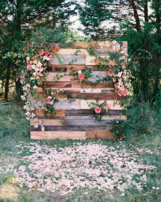 a reclaimed wood wedding backdrop with greenery, blush and bold blooms and petals on the ground is chic