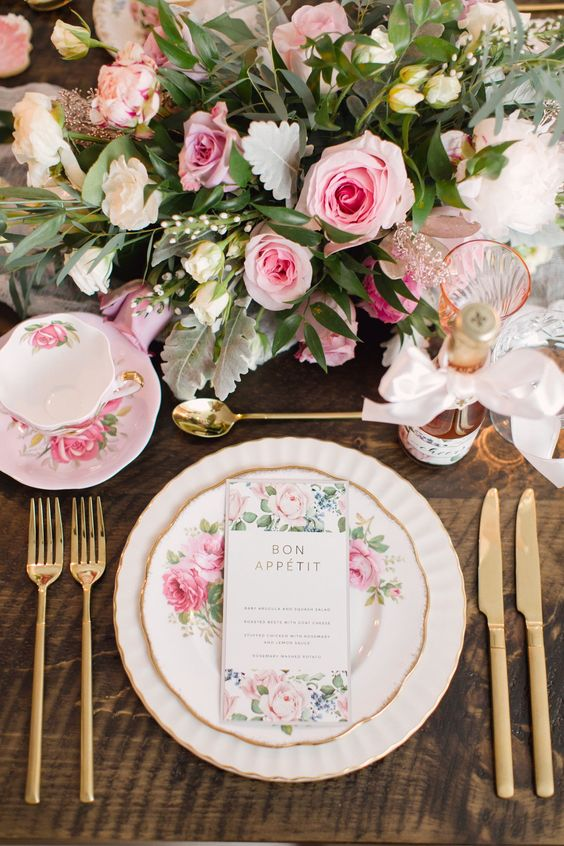 a refined and romantic sprign bridal shower tablescape with floral plates and teaware, pink blooms and gold touches