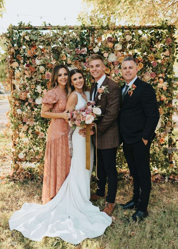a refined backyard wedding backdrop covered with greenery, neutral and pastel blooms looks very chic and stylish