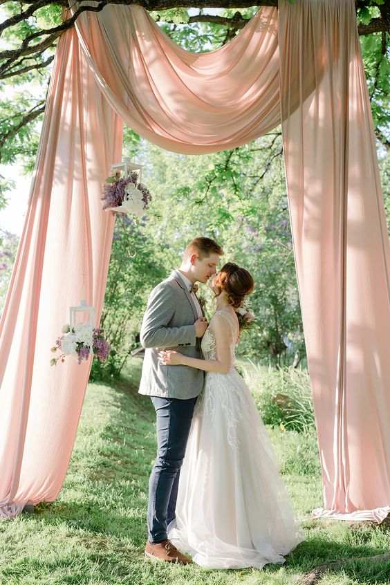 a refined backyard wedding ceremony space with blush fabric, candle lanterns with blooms hanging down from the branches