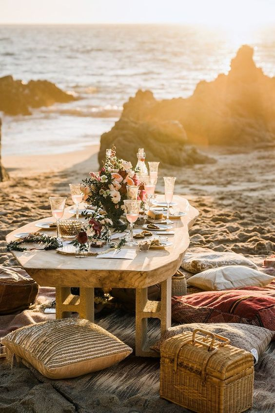 a romantic boho beach wedding picnic space with rugs, pillows, a wicker chest, a low table, bright blooms and candles