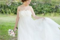a romantic empire waist wedding ballgown with a floral applique bodice and a layered skirt, statement earrings
