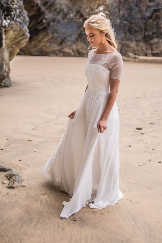 a romantic flowy a-line wedding dress with an illusion neckline and sleeves, lace appliques and a flowy skirt