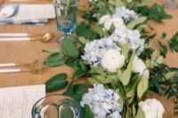 a romantic pastel blue wedding tablescape with blue and neutral blooms, greenery, blue menus and glasses